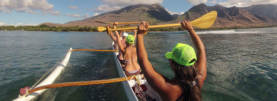 people raising paddles in outrigger canoe