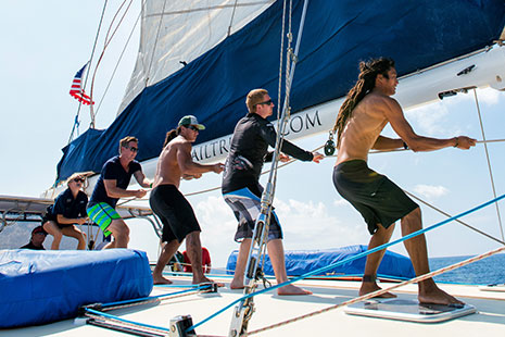 Trilogy crew raising the sails